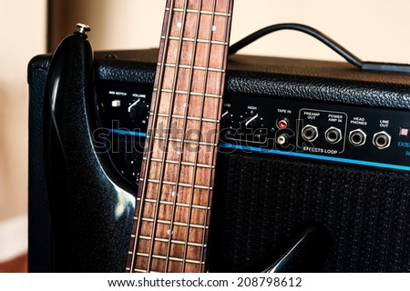 Five string bass guitar and amplifier. Selective focus - stock photo