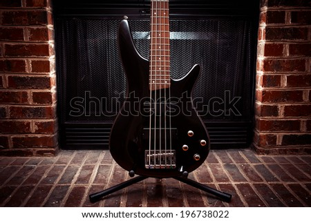 Five string bass guitar in front of fireplace - stock photo