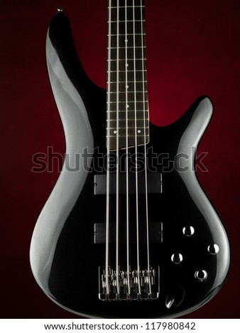 Five string electric bass guitar over red background, for music,entertainment themes - stock photo