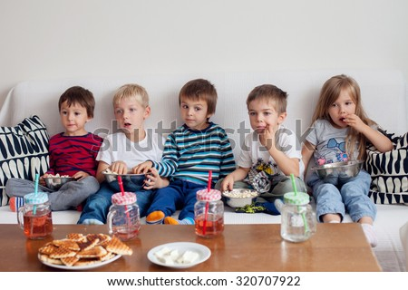 Five sweet kids, friends, sitting in living room at home, watching TV and eating popcorn - stock photo
