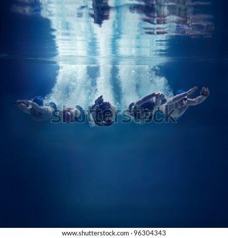 Five swimmers jumping together into water isolated blue background - stock photo