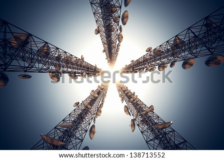 Five tall telecommunication towers with antennas on blue sky. View from the bottom. - stock photo