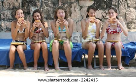 Five teenage girls eating hamburgers on the beach - stock photo