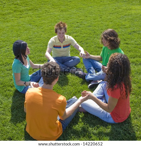 Five teens hold hands at a park