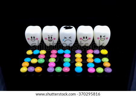 Five teeth smile and cry emotion on black background, Happy New Year 2016 arranged from Chocolate candy, Dental Health concept. - stock photo