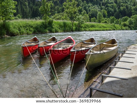 Five tied, empty canoes lie in a row next to each other in a river on a fortified landing stage on the shore.  - stock photo