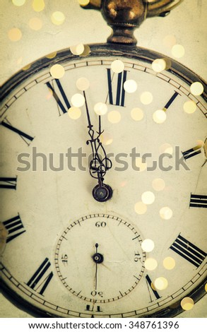 Five to twelve. Clock face and party lights decoration. Vintage style toned picture - stock photo