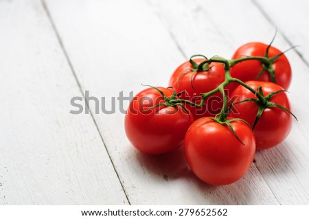 Five tomatoes on branch with white wooden background