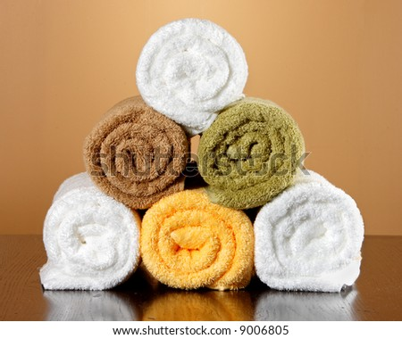 Five towels stacked up on a table with a reflection - stock photo