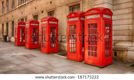 Five traditional old style UK red phone boxes in Covent Garden in London on a sunny day - stock photo