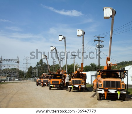 Five utility bucket trucks parked beside an electrical substation. - stock photo