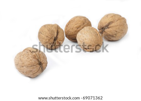 Five walnuts lie on a white background, focus in the image center, a shot horizontal - stock photo