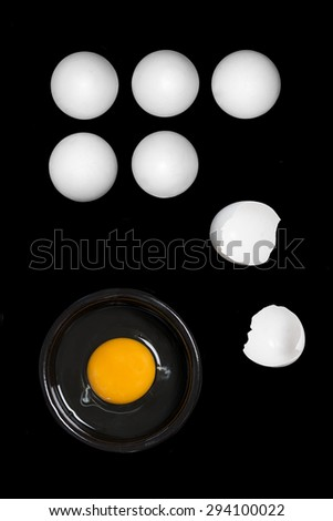 five white eggs and a broken egg on a black background - stock photo