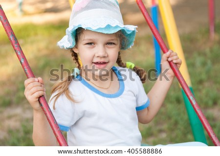 Five-year girl in summer panama rides on a swing - stock photo