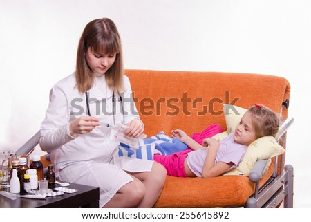 Five-year girl looks frightened as doctor is preparing to make her a shot - stock photo