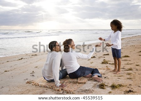 Five year old African-American girl finding shells with parents on beach - stock photo
