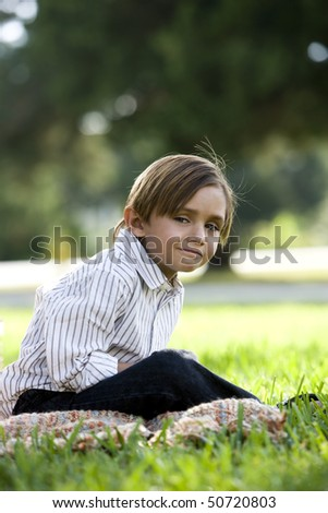 Five year old boy sitting on blanket in park - stock photo