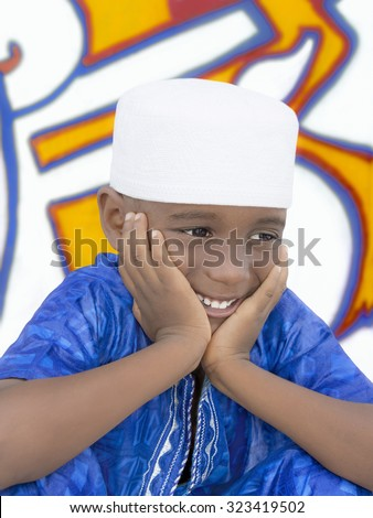 Five-year-old boy wearing a blue garment and a white hat - stock photo