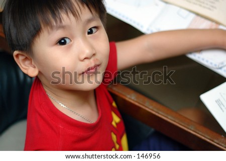 Five-year old Chinese boy learning to write in Penang, Malaysia - stock photo