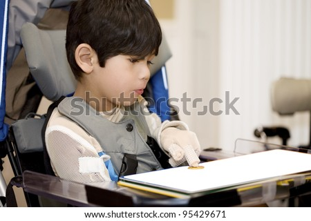 Five year old disabled boy studying in wheelchair, pointing at object on book - stock photo