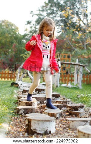 Five year old girl walking over pebbles. Sensory Discovery Walk. Sensory garden. - stock photo