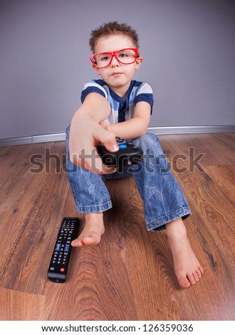 Five years old boy watching tv - stock photo