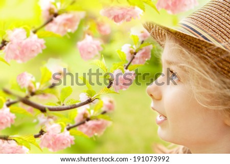 Five years old caucasian blond child girl in a hat looking at Flowering Almond (Prunus triloba) blossom in spring garden. Discovering beauty of nature - happy careless childhood. - stock photo