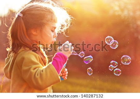 Five years old caucasian child girl blowing soap bubbles outdoor at sunset - happy carefree childhood - stock photo