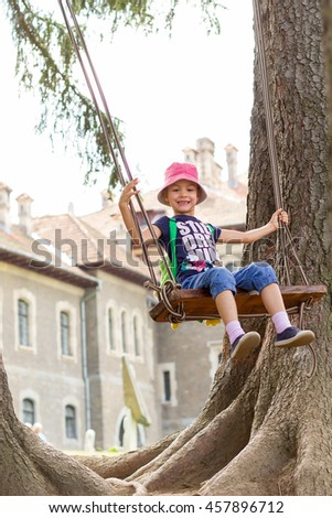Five years old girl playing on a giant fir trees swing with castle behind. - stock photo