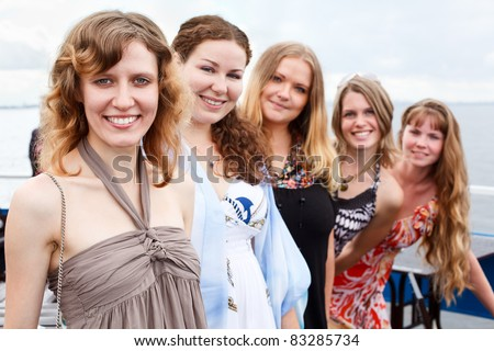 Five young beautiful women are standing in line. Caucasian people. Summer time
