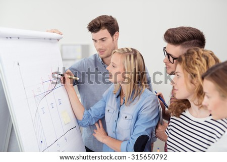 Five Young Businesspeople Making a Conceptual Business Graph on a Poster Paper Together Inside the Office. - stock photo