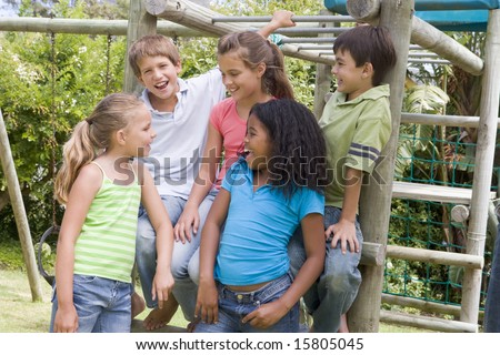 Five young friends at a playground smiling - stock photo