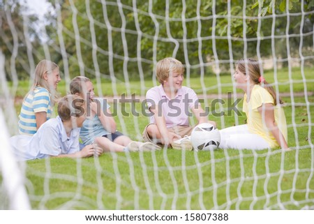 Five young friends on soccer field talking and smiling - stock photo