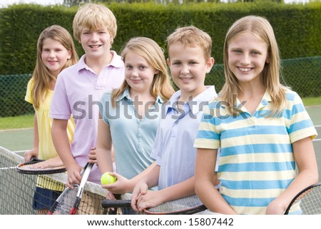 Five young friends with rackets on tennis court smiling - stock photo