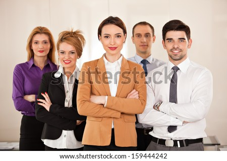 Five young gorgeous business people smiling  with their arms crossed - stock photo