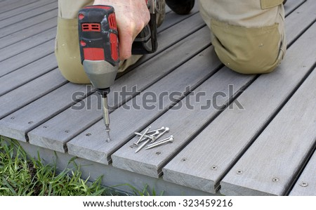 fixing composite decking with a screw gun - stock photo