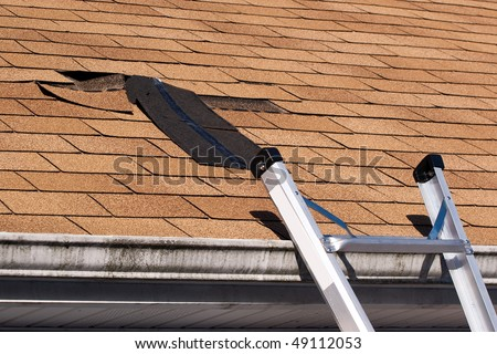 Fixing damaged roof shingles.  A section was blown off after a storm with high winds causing a potential leak. - stock photo