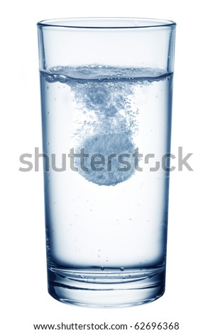 Fizzy pill in the glass of water. Isolated on a white background.