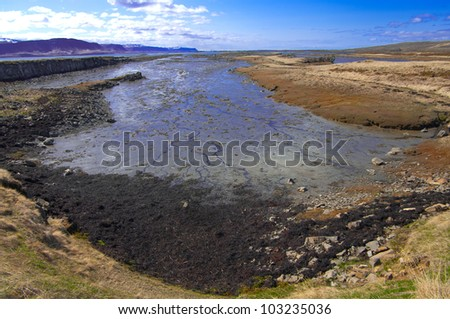 Fjord at Low Tide:  The shallow bottom at the end of an Icelandic fjord is visible between tides. - stock photo