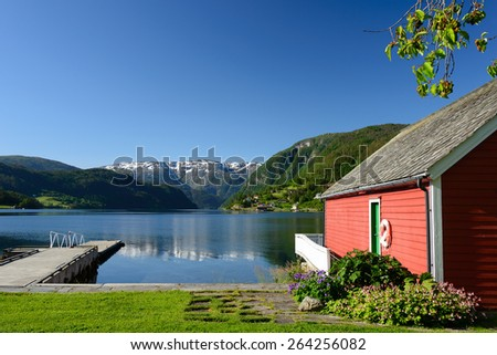 Fjord view over Hardangerfjord with a red boathouse (naust) and a small pier in Ulvik in Hordaland county, Norway. - stock photo