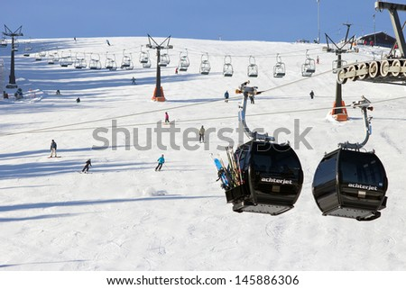 FLACHAU, AUSTRIA - DEC 29: Ski lift cable booths going up the piste in Flachau, Austria on Dec 29, 2012. These pistes are part of the Ski Armada network, the largest of Europe.  - stock photo