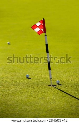 Flag and 3 balls on the golf course.
