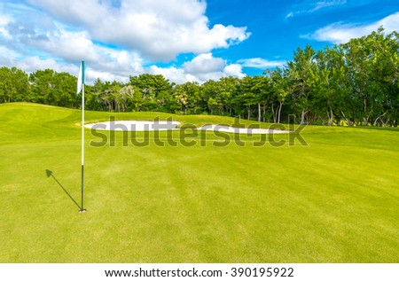 Flag and sand bunkers at the beautiful golf course. - stock photo