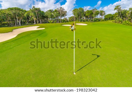 Flag and sand bunkers at the beautiful golf course of the luxury Mexican resort. - stock photo
