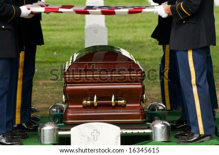 Flag being lifted from casket during burial at Arlington National Cemetery - stock photo