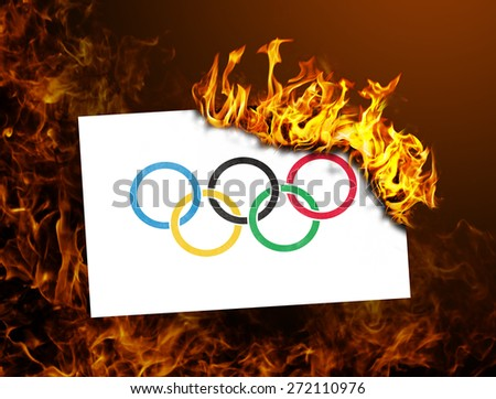 Flag burning - concept of war or crisis - Olympic rings - stock photo