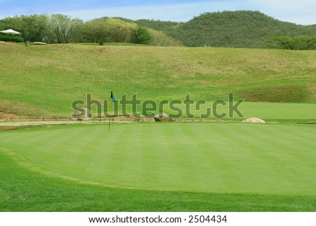 Flag in the hole on the South African golf course. - stock photo