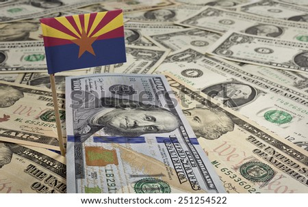 Flag of Arizona sticking in a variety of american banknotes.(series) - stock photo