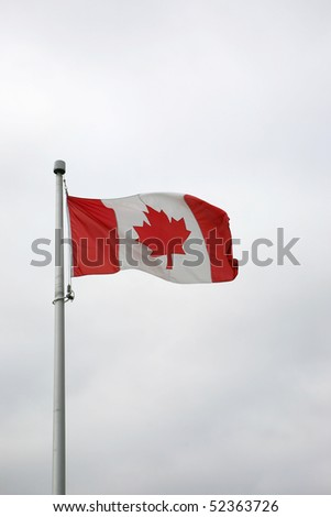 flag of canada in front of a stormy sky