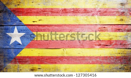 Flag of Catalonia painted on grungy wooden background - stock photo